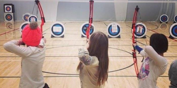 Girls practicing archery in a gymnasium.